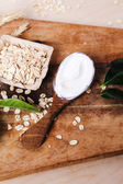 Yoghurt in wooden spoon and oatmeal — Stock Photo