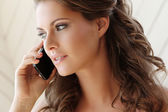 Girl talking on phone at home — Stock Photo