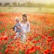 Woman with child in field with poppies — Stock Photo #73786115
