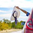 Woman shows sun hat from car — Stock Photo #62436169