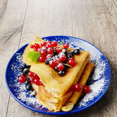 Crepes with blueberries and redcurrant — Stock Photo