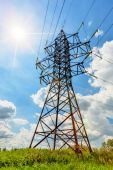 High voltage line and sun in cloudy sky — Stock Photo
