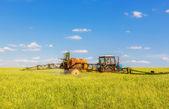 Сельское хозяйство, трактора, опрыскивание зеленое поле — Стоковое фото