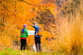 Couple hiking with map in autumn forest — Stock Photo