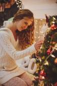 Girl decorates a Christmas tree — Stock Photo