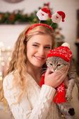 Girl with a cat in the cap of Santa — Stock Photo