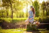 Young woman sitting near pond — Stock Photo