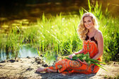 Blonde woman sitting near the river — Stock Photo