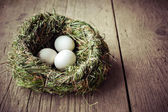 Title: Organic white eggs in hay nest at wooden table. Eco food composition — Stock Photo