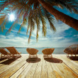 Tropical beach with palm tree and chairs for relaxation on woode — Stock Photo #54501525