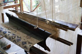 Vintage manual weaving loom with unfinished textile work — Stock Photo