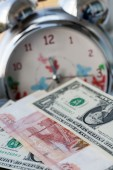 Russian and American money on a background of the alarm. Time is money — Stock Photo