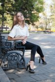 Young girl sitting on a bench in autumn park — Stock Photo