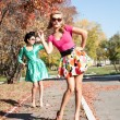 Two girls in colorful dresses walking in the autumn park — Stock Photo #53980617