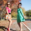 Two girls in colorful dresses walking in the autumn park — Stock Photo #53980621
