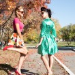 Two girls in colorful dresses walking in the autumn park — Stock Photo #53980631