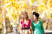 Two girls on the background of bright autumn leaves of birch — Stock Photo