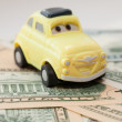 Toy car on a background of US dollars banknotes — Stock Photo #58992357