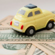 Toy car on a background of US dollars banknotes — Stock Photo #58992361
