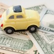 Toy car on a background of US dollars banknotes — Stock Photo #58992377