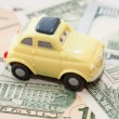 Toy car on a background of US dollars banknotes — Stock Photo #58992387