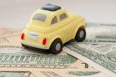 Toy car on a background of US dollars banknotes — Stockfoto