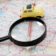 Toy car, pencil and magnifying glass on a road atlas — Stock Photo #59063523