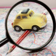Toy car, pencil and magnifying glass on a road atlas — Stock Photo #59063527