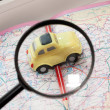 Toy car, pencil and magnifying glass on a road atlas — Stock Photo #59063529