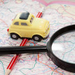 Toy car, pencil and magnifying glass on a road atlas — Stock Photo #59063531