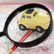 Toy car, pencil and magnifying glass on a road atlas — Stock Photo #59063533