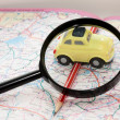 Toy car, pencil and magnifying glass on a road atlas — Stock Photo #59063535