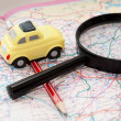 Toy car, pencil and magnifying glass on a road atlas — Stock Photo #59063539