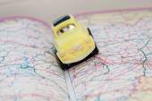 Toy car on a road atlas. The concept of travel planning. — Stock Photo