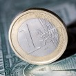 One euro coin on a dollar bill — Stockfoto #64372855