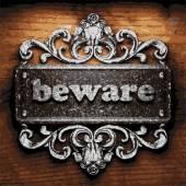 Beware vector metal word on wood — Stock Vector