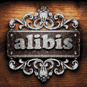 Alibis vector metal word on wood — Stock Vector