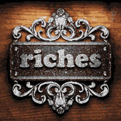 Riches vector metal word on wood — Stock Vector