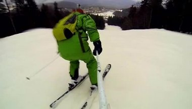 Skier going downhill  with camera on his helmet and in hand — Vídeo de Stock