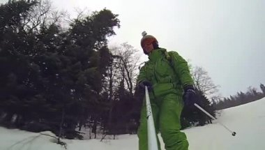Skier going downhill  with camera on his helmet and in hand — Stockvideo