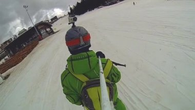 Skier going downhill  with camera on his helmet and in hand — Stock Video