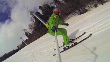 Лыжник, спускающийся с камерой на его шлеме и в руке — Стоковое видео