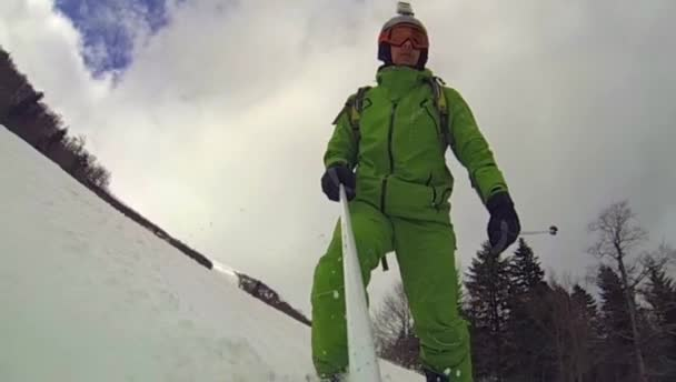 Skier going downhill  with camera on his helmet and in hand — Vidéo