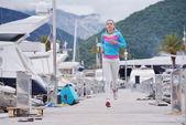 Woman jogging in marina — Stock Photo