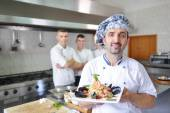 Group of handsome chefs dressed in white uniform — Stock Photo