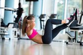 Woman stretching and warming up at a gym — Stock Photo