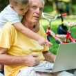 Grandfather and child using laptop computer — Stock Photo #65942023