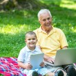 Grandfather and child using laptop and tablet computer — Stock Photo #65946941