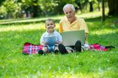 Grandfather and child using laptop and tablet computer — Stock Photo