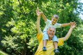 Grandfather and child have fun in park — Zdjęcie stockowe
